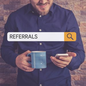 Man holding phone and coffee with search bar with the text referrals